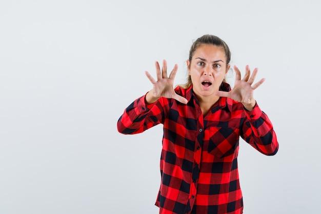 Jonge dame die doet alsof ze iets in een geruit overhemd grijpt en er gek uitziet