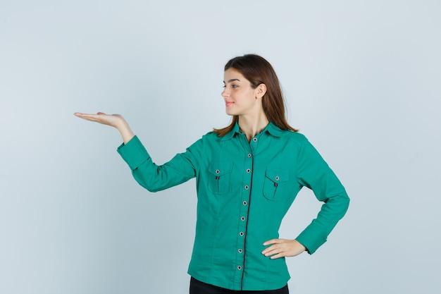Jonge dame die doet alsof ze iets in een groen overhemd vasthoudt en er zelfverzekerd uitziet, vooraanzicht.