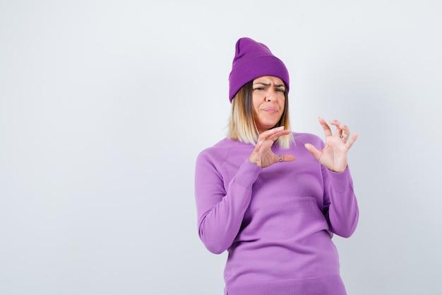 Jonge dame die doet alsof ze iets in een paarse trui, muts vangt en er ontevreden uitziet, vooraanzicht.