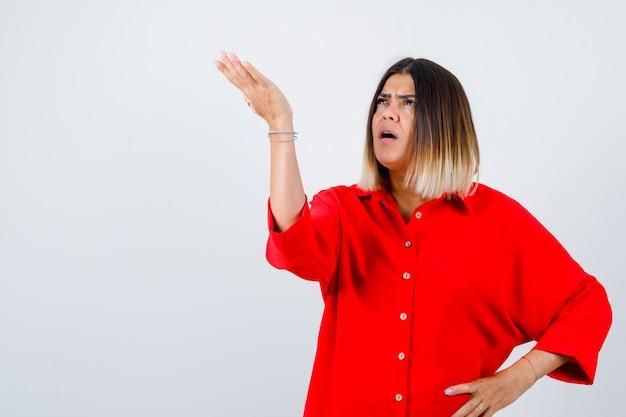 Jonge dame die doet alsof ze iets in een rood oversized shirt laat zien en er serieus uitziet, vooraanzicht.