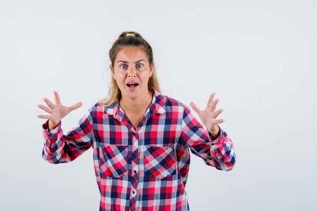 Jonge dame die doet alsof ze iets vangt in een geruit overhemd en opgewonden kijkt, vooraanzicht.