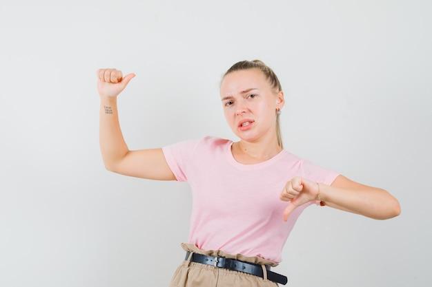 Jonge dame die doet alsof ze iets vasthoudt, duim in t-shirt en broek toont en ontevreden kijkt, vooraanzicht