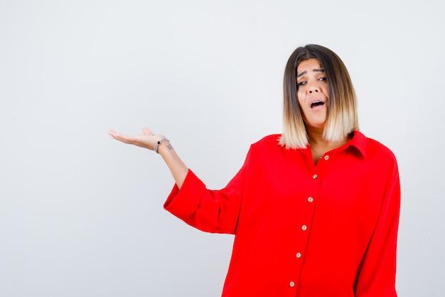 Jonge dame die doet alsof ze iets vasthoudt of laat zien in een rood oversized shirt en er angstig uitziet. vooraanzicht.