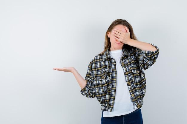 Jonge dame die doet alsof ze iets vasthoudt terwijl ze de ogen bedekt met hand in een t-shirt, jas, spijkerbroek en er serieus uitziet, vooraanzicht.