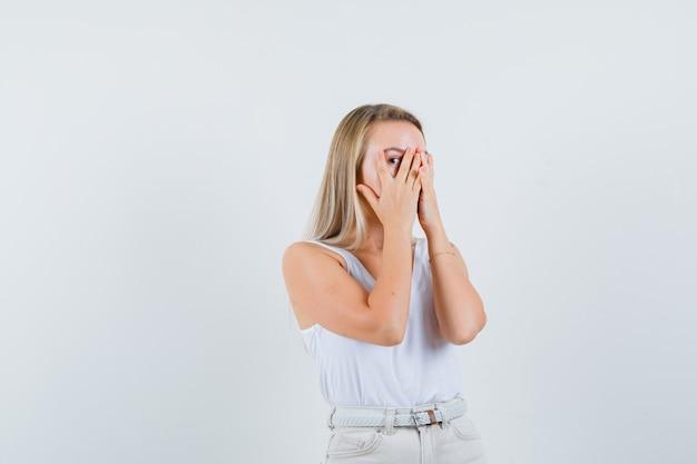 Jonge dame die door vingers in witte blouse kijkt en opgewekt kijkt