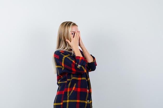 Jonge dame die door vingers kijkt terwijl handen op gezicht in geruit overhemd kijkt en schattig, vooraanzicht kijkt.