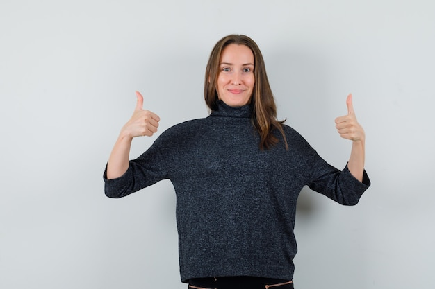 Jonge dame die dubbele duimen in overhemd toont en zelfverzekerd kijkt