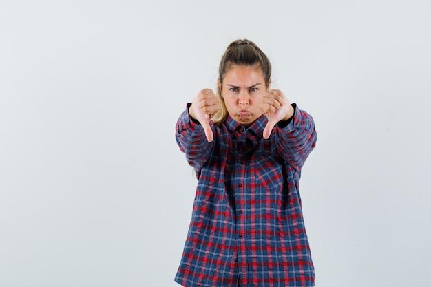 Jonge dame die dubbele duimen neer in geruit overhemd toont en teleurgesteld kijkt. vooraanzicht.