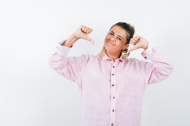 Jonge dame die dubbele duimen neer in roze overhemd toont en er zelfverzekerd uitziet