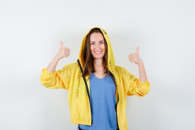 Jonge dame die dubbele duimen toont in t-shirt, jas en er gelukkig uitziet. vooraanzicht.
