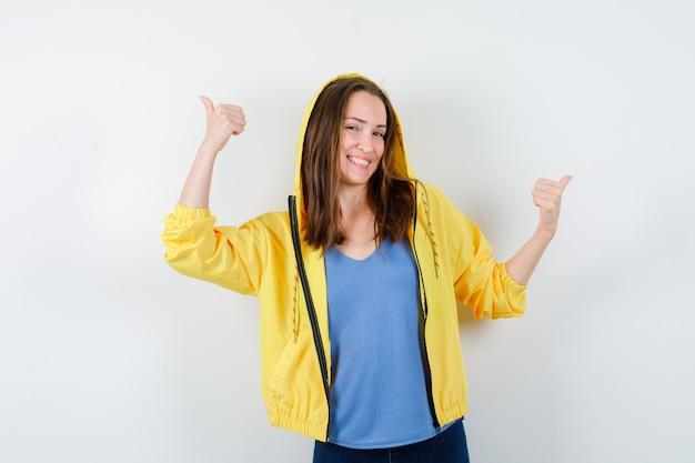 Jonge dame die dubbele duimen toont in t-shirt, jasje en er zelfverzekerd uitziet