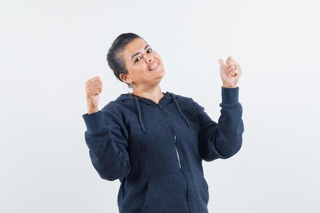 Jonge dame die duim in jasje toont en positief kijkt