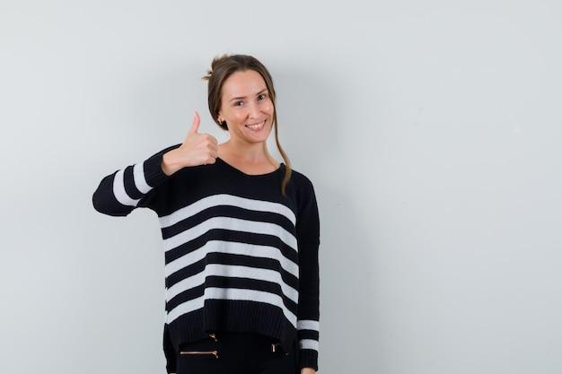 Jonge dame die duim in overhemd toont en vrolijk kijkt