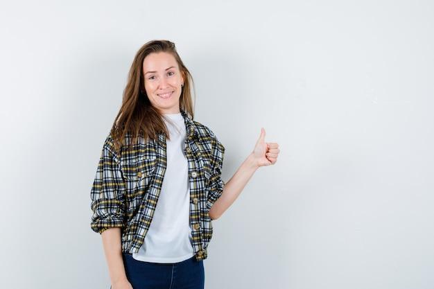 Jonge dame die duim in t-shirt, jasje, spijkerbroek toont en er aantrekkelijk uitziet, vooraanzicht.