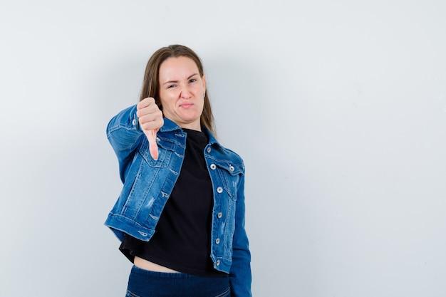 Jonge dame die duim naar beneden in blouse, jas toont en er ontevreden uitziet. vooraanzicht.