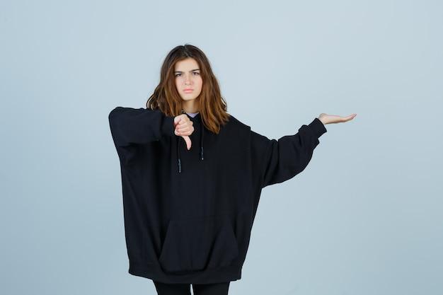Jonge dame die duim naar beneden laat zien terwijl ze iets laat zien in een oversized hoodie, broek en er weemoedig uitziet. vooraanzicht.