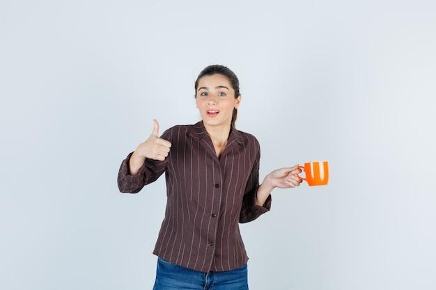 Jonge dame die duim opduikt in shirt, spijkerbroek en er attent uitziet, vooraanzicht.