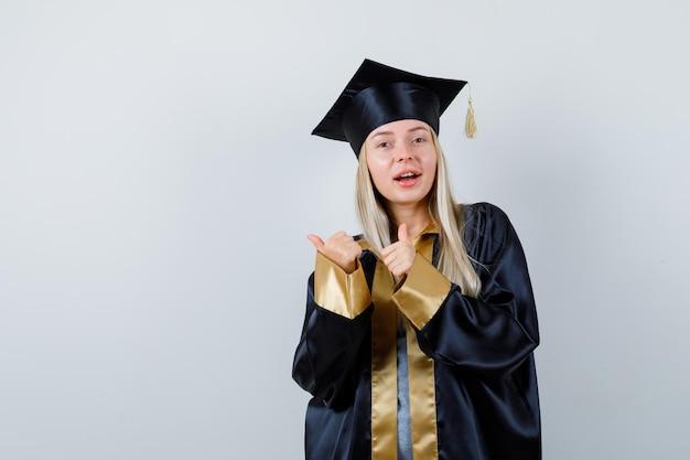 Jonge dame die duimen opduikt in academische kleding en er gelukkig uitziet