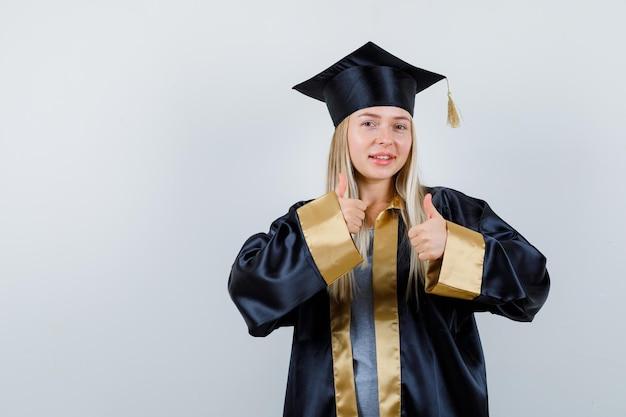 Jonge dame die duimen opduikt in academische kleding en er zelfverzekerd uitziet.