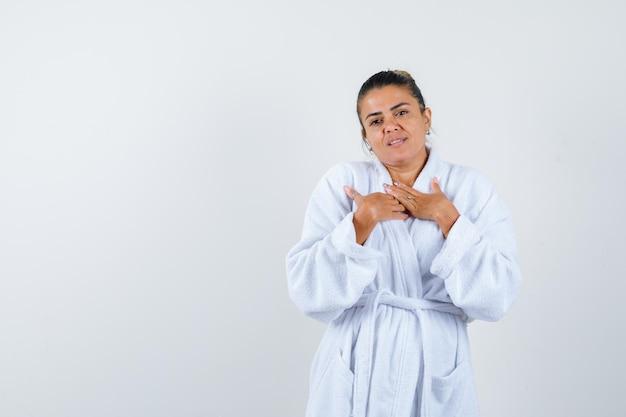 Jonge dame die een gebedsgebaar in badjas toont en er hoopvol uitziet