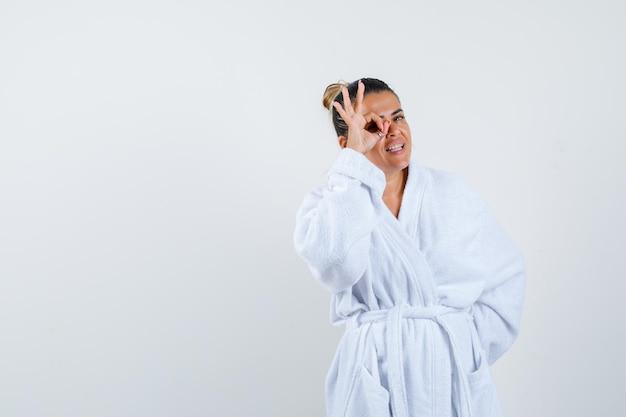 Jonge dame die een goed gebaar in badjas toont en er schattig uitziet