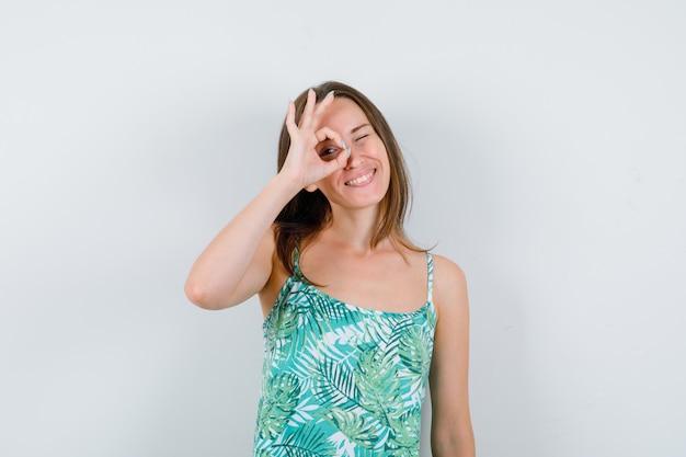 Jonge dame die een goed gebaar in blouse toont en er gelukkig uitziet, vooraanzicht.