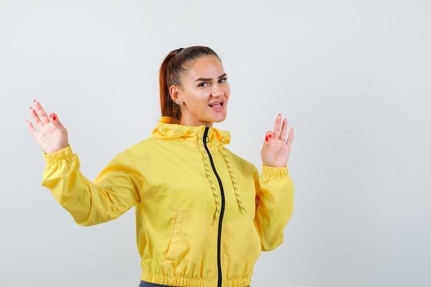 Jonge dame die een goed gebaar in een geel jasje toont en er vrolijk uitziet. vooraanzicht.
