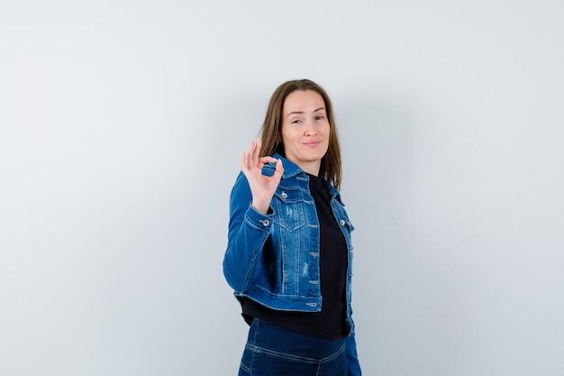Jonge dame die een goed gebaar in shirt, jas toont en er zelfverzekerd uitziet. vooraanzicht.