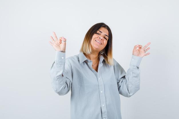 Jonge dame die een goed gebaar toont in een oversized shirt en er vrolijk uitziet. vooraanzicht.