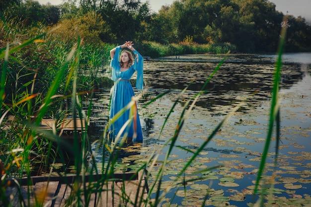 Jonge dame die een jurk draagt, stelt in een water