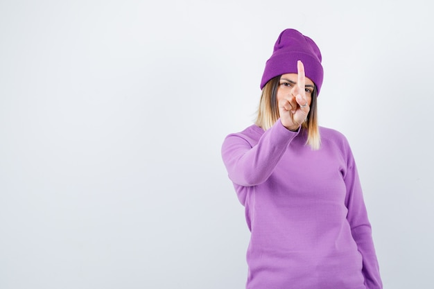 Jonge dame die een klein gebaar toont in paarse trui, muts en er zelfverzekerd uitziet. vooraanzicht.