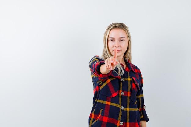 Jonge dame die een minuut gebaar in een geruit overhemd toont en er zelfverzekerd uitziet, vooraanzicht.