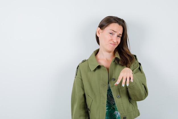 Jonge dame die een stopgebaar in een groen jasje toont en er ontevreden uitziet, vooraanzicht.