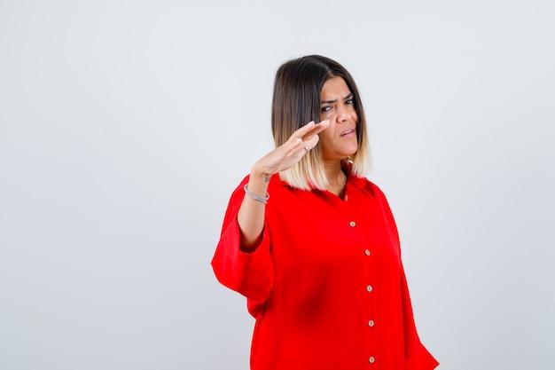 Jonge dame die een stopgebaar in een rood oversized shirt toont en er zelfverzekerd uitziet, vooraanzicht.