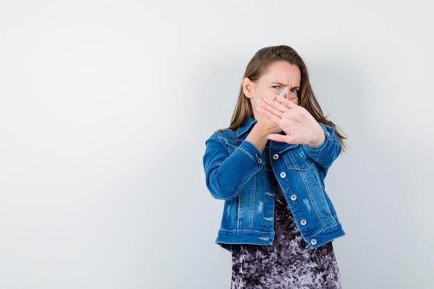 Jonge dame die een stopgebaar toont, de hand op de mond houdt in een jurk, een spijkerjasje en er walgelijk uitziet. vooraanzicht.