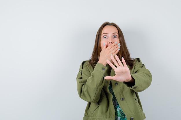 Jonge dame die een stopgebaar toont, met de hand op de mond in een groen jasje en er doodsbang uitziet, vooraanzicht.