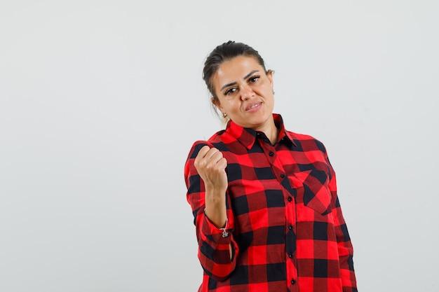 Jonge dame die gebalde vuist in geruit overhemd opheft en zelfverzekerd kijkt