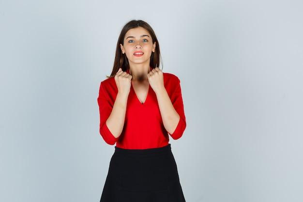 Jonge dame die gebalde vuisten in rode blouse, rok toont en vrolijk kijkt