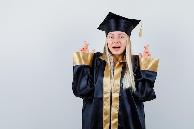 Jonge dame die gekruiste vingers in academische kleding toont en er schattig uitziet