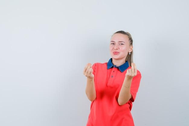 Jonge dame die geldgebaar in t-shirt toont en blij kijkt