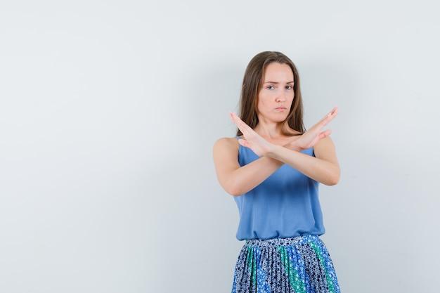 Jonge dame die gesloten gebaar in blouse, rok toont en ernstig, vooraanzicht kijkt.