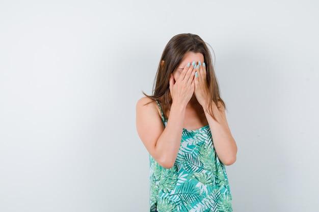 Jonge dame die gezicht bedekt met handen en er depressief uitziet. vooraanzicht.