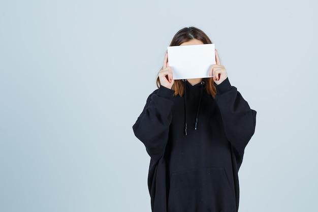 Jonge dame die gezicht bedekt met papier in een oversized hoodie, broek en er schattig uitziet, vooraanzicht.