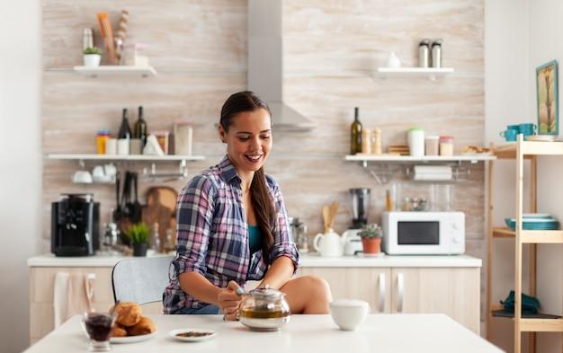 Jonge dame die groene thee drinkt en lacht bij het ontbijt zittend aan de tafel in de keuken