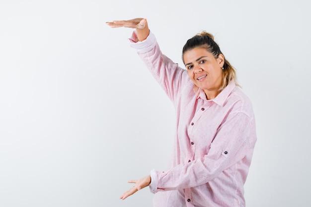 Jonge dame die groot formaatteken in roze overhemd toont en er zelfverzekerd uitziet