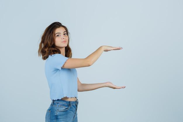 Jonge dame die groot formaatteken toont terwijl zij camera in t-shirt, jeans bekijkt en gelukkig, vooraanzicht kijkt.