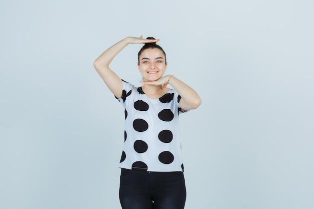Jonge dame die grootteteken in t-shirt, jeans toont en gelukkig kijkt. vooraanzicht.
