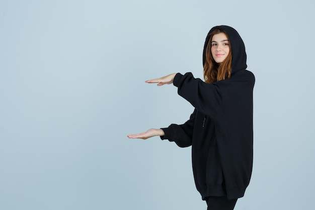 Jonge dame die grootteteken toont in oversized hoodie, broek en er zelfverzekerd uitziet. vooraanzicht.