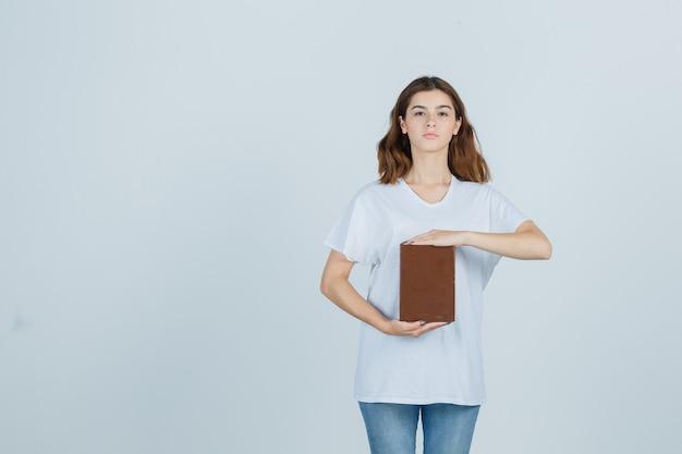 Jonge dame die grootteteken toont terwijl ze boek in t-shirt, spijkerbroek vasthoudt en er zelfverzekerd uitziet, vooraanzicht.