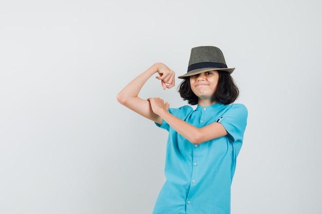Jonge dame die haar armspier in blauw overhemd, hoed toont en gelukkig kijkt